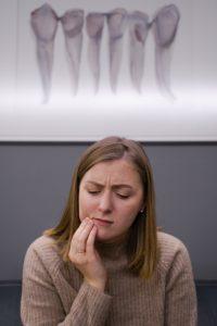 Woman in pain needing an emergency dentist.