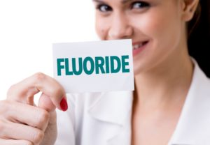 Woman showing benefits of fluoride on teeth.