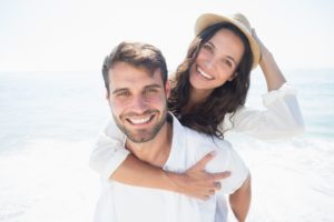 young couple on the beach after seeing their cosmetic dentist